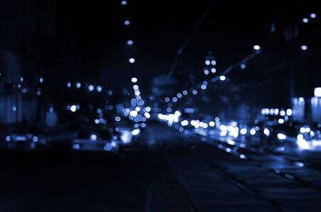 Nights lights of the big city, the blurred night avenue with bokeh traffic lights and headlights of the approaching cars. phantom classic blue color
