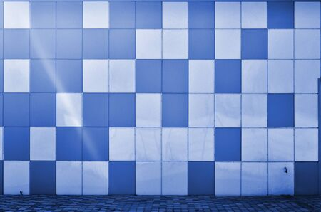 The texture of the metal wall, framed in the form of colored squares. Modern wall design for the exterior of residential and office buildings. phantom classic blue color