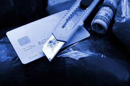 Spoon full of heroin and paper knife lies on drug packs and credit card with dollars roll. Concept of drug trafficking and dealing in United States territory. phantom classic blue color Фото со стока
