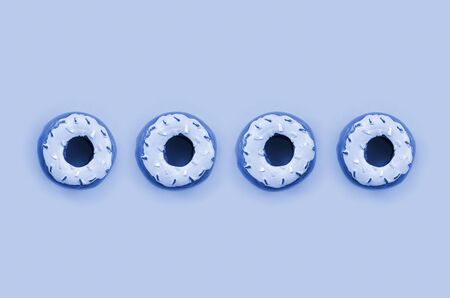 Many small plastic donuts lies on a phantom classic blue background. Flat lay minimal pattern. Top view.