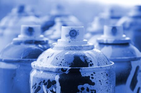 A lot of dirty and used aerosol cans of phantom classic blue color paint. Macro photograph with shallow depth of field. Selective focus on the spray nozzle. Фото со стока