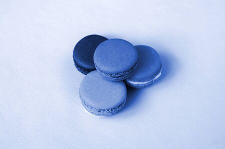 Dessert cake macaron or macaroon on phantom classic blue color background. Fashionable tasty colorful cookies.