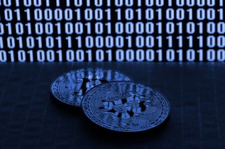 A pair of bitcoins lies on a cardboard surface on the background of a monitor depicting a binary code of bright zeros and one units on a black background. phantom classic blue color