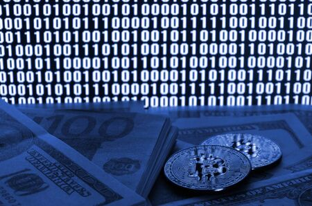 Two bitcoins lies on a pile of dollar bills on the background of a monitor depicting a binary code of bright zeros and one units on a black background. phantom classic blue color. Фото со стока