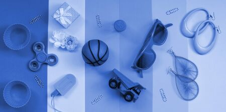 Trendy pastel composition with earrings, sunglasses, beverage can, basketball ball, toy truck, gift box, ice cream, flower and spinner. phantom classic blue color.