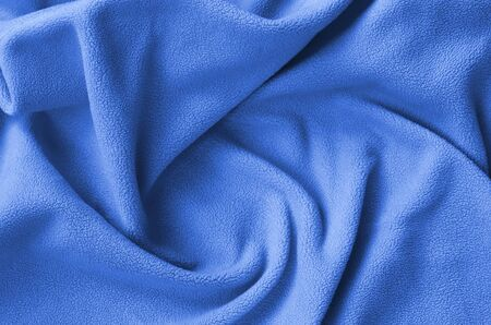The blanket of furry fleece fabric. A background of soft plush fleece material with a lot of relief folds. phantom classic blue color.