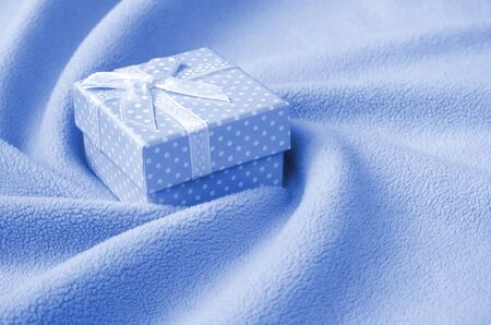 A small gift box with a small bow lies on a blanket of soft and furry phantom classic blue color fleece fabric with a lot of relief folds. Packing for a gift to your lovely girlfriend.