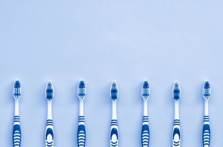 A lot of toothbrushes lie on a phantom classic blue color background. Top view, flat lay. Minimal concept. Фото со стока