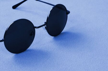 Stylish black sunglasses with round glasses lies on a blanket made of soft and fluffy phantom classic blue color fleece fabric. Fashionable background picture. Фото со стока
