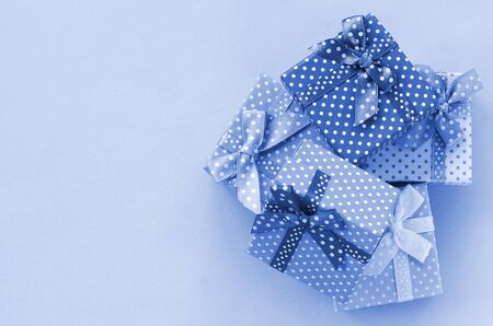 Pile of a small colored gift boxes with ribbons lies on a phantom classic blue color background. Minimalism flat lay top view.