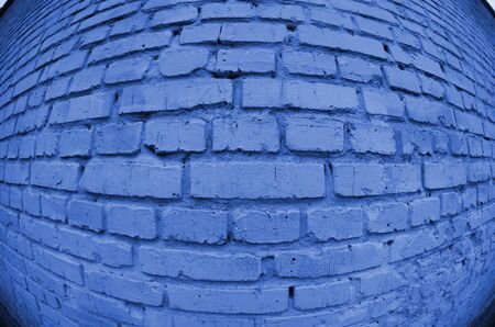 Large brick wall, painted in phantom, classic, blue, trendy, color, 2020, year, fashion, new, style. Fisheye photo with pronounced distortion.