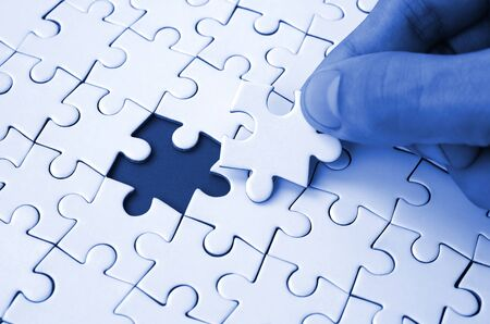 The human hand fills the last missing elements of the surface from the jigsaw puzzle. The concept of the completion of the initiated cases. phantom classic blue color tone.