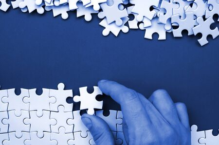 The hand folds a white jigsaw puzzle and a pile of uncombed puzzle pieces lies against the background of phantom classic blue color surface. Texture photo with space for text.