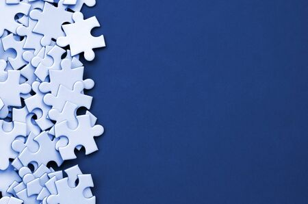 A pile of uncombed elements of a white jigsaw puzzle lies on the background of a phantom classic blue color surface. Texture photo with copy space for text