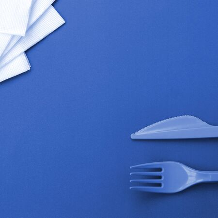 Disposable plastic cutlery. Plastic fork and knife lie on phantom classic blue color background surface next to napkins
