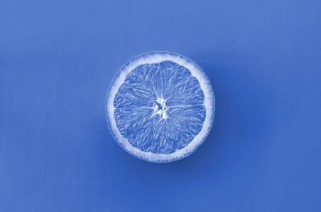 Top view of a one orange fruit slice on bright background in phantom classic blue color color. A saturated citrus texture image. Фото со стока