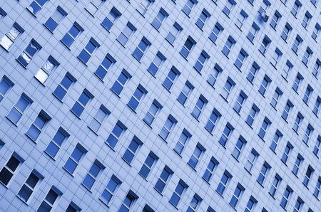 A pattern of many windows from a multi-storey office building. A large number of plastic windows in the wall of a modern multi-storey building. phantom classic blue color Фото со стока