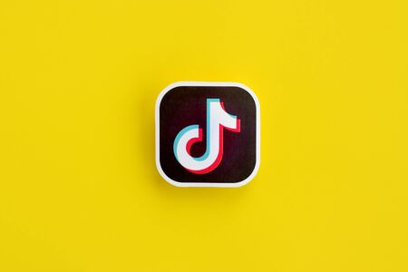 NY, USA - DECEMBER 5, 2019: Tiktok paper logo on yellow background. TikTok is a popular video-sharing social networking service owned by ByteDance