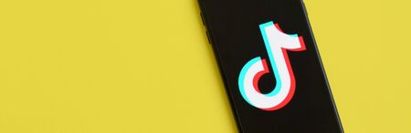 NY, USA - DECEMBER 5, 2019: Tiktok logo on samsung smartphone screen on yellow background. TikTok is a popular video-sharing social networking service owned by ByteDance