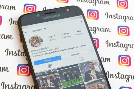 NY, USA - DECEMBER 4, 2019: Cristiano Ronaldo official instagram account on smartphone screen on paper instagram banner.