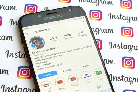 NY, USA - DECEMBER 4, 2019: Ronaldinho official instagram account on smartphone screen on paper instagram banner.