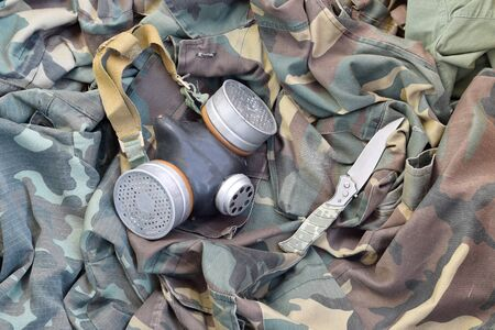Stalker soldiers soviet gas mask lies with knife on green khaki camouflage jackets. Post apocalypse surviving items kit
