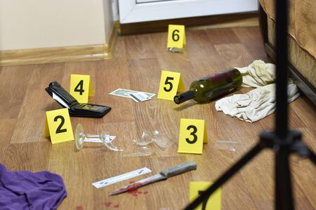 Crime scene investigation - numbering of evidences after the murder in the apartment. Broken glass of wine, knife with clothes, wallet and bottle as evidence close up