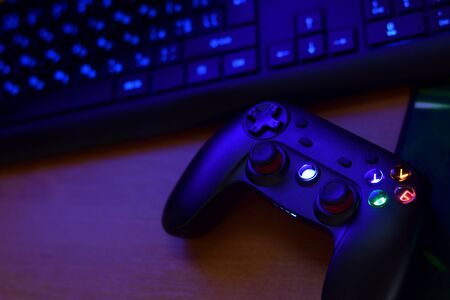 Modern gamepad lies with keyboard on table in dark playroom scene close up. Video game challenges and competitions concept Imagens