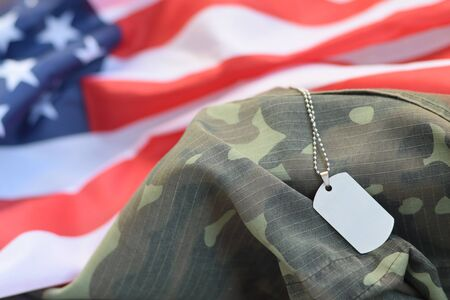 Silvery military beads with dog tag on United States fabric flag and camouflage uniform. Army token on USA banner close up. Memorial day concept