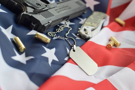 Army Dog tag token with 9mm bullets and pistol lie on folded United States flag. A set of US military veteran items or old duty trophy kit