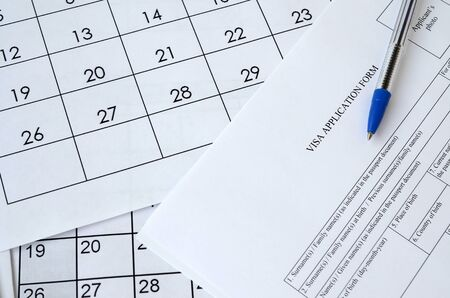 Typical Visa application form and blue pen on paper calendar page close up Banco de Imagens