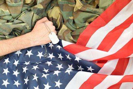 Male hand holds dog tag on USA flag and military uniform background. Concept of joining the US military