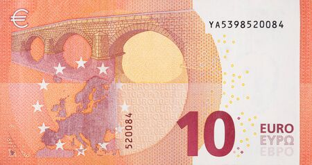 Fragment part of 10 euro banknote close-up with small red details. European currency bill
