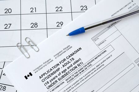 Application for Canadian citizenship for adults and blue pen lies on calendar page close up Stock fotó