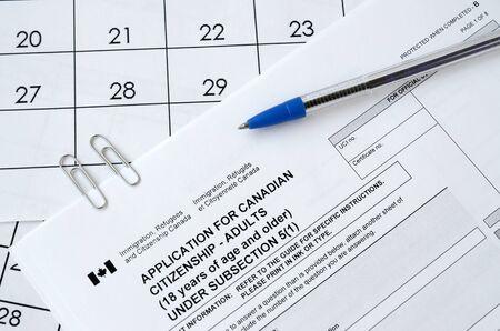 La demande de citoyenneté canadienne pour les adultes et le stylo bleu se trouve sur la page du calendrier en gros plan Banque d'images