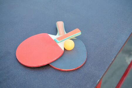 rackets and ball close up on table tennis rable in outdoor sport yard. Active sports and physical training concept Stock Photo