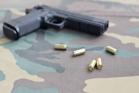 Las balas de 9 mm y la pistola se encuentran sobre una tela verde camuflaje. Un conjunto de artículos para el campo de tiro o un equipo de defensa personal. Conchas de oro cerca de pistola