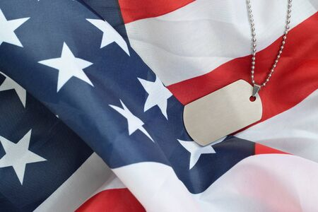 Silvery military beads with dog tag on United States fabric flag. Army token on USA banner close up. Memorial day concept Stock Photo