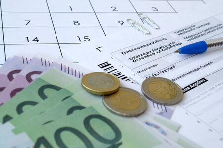 Le formulaire fiscal allemand avec stylo et factures européennes se trouve sur le calendrier du bureau. Contribuables en Allemagne utilisant l'euro pour payer leurs impôts annuels Banque d'images