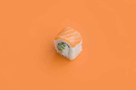 Philadelphia roll with salmon on orange background close up. Minimalism top view flat lay with Japanese food