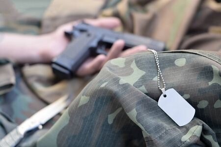 Army token lies on camouflage uniform of dead soldier and hand with pistol. Concept of war actions between East Ukraine and Russia