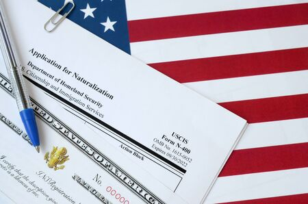 N-400 Application for Naturalization and Certificate of naturalization lies on United States flag with blue pen from Department of Homeland Security close up Reklamní fotografie