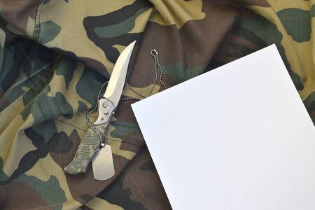 Blank paper with knife and army dog tag lies on camouflage military uniform. Copy space for notes during military service period