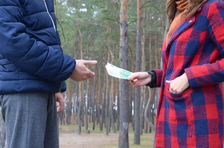 A girl transfers euro bills to the hands of a young guy in autumn forest. Concept of robbery or illegal deal transaction