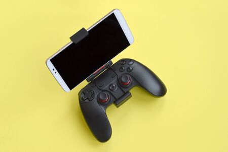 Modern black gamepad for smartphone on yellow background close up. Mobile video gaming device
