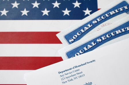 United States social security number cards lies with USCIS envelope on US flag close up