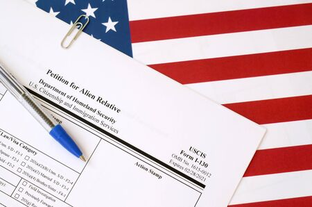 I-130 Petition for alien relative blank form lies on United States flag with blue pen from Department of Homeland Security close up Stok Fotoğraf