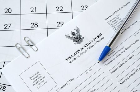 Thailand Visa application form and blue pen on paper calendar page close up Stock Photo