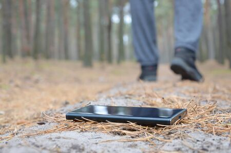 Young boy loses his smartphone on Russian autumn fir wood path. Carelessness and losing expensive mobile device concept Zdjęcie Seryjne