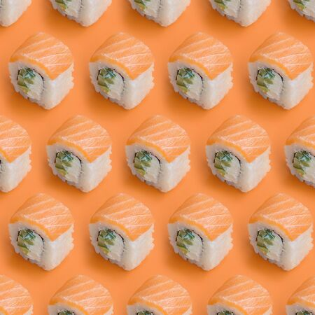 Philadelphia rolls with salmon on orange background close up. Minimalism top view flat lay pattern with Japanese food